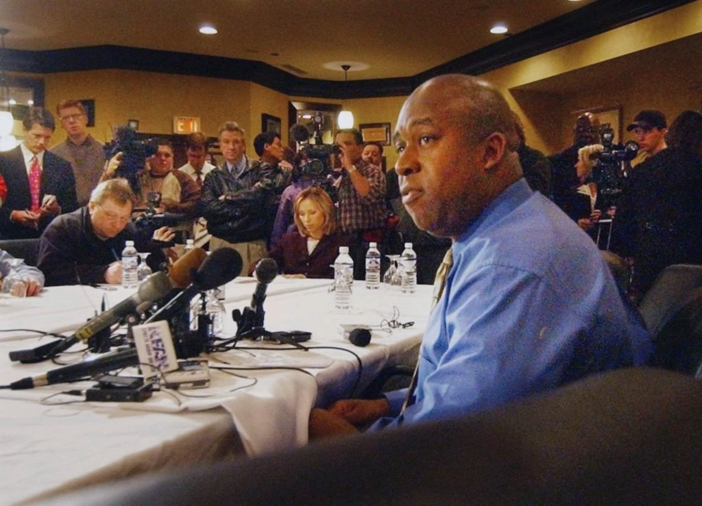 A pensive black man is the subject of a press conference