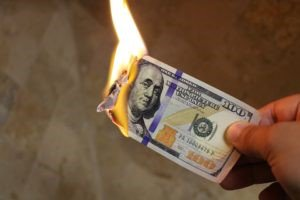 Hand holding a burning $100 bill